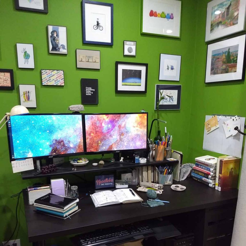 dark brown desk with piles of books, notebooks, dual monitor; green walls with many postcards and other art framed hanging on walls