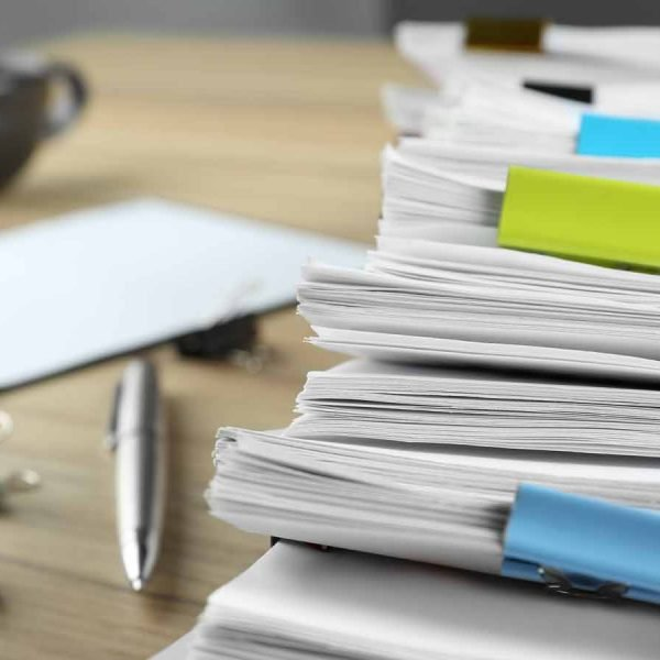 Stack of documents with binder clips and pen on wooden table, closeup view