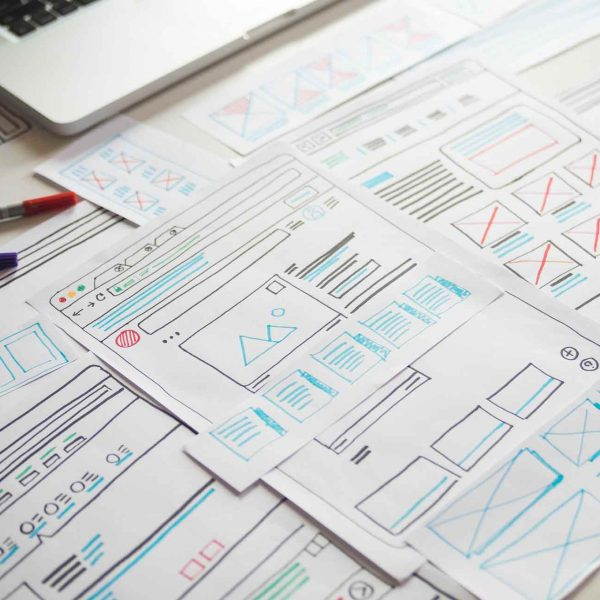 hand drawn wireframes on white surface, pens off to one side and corner of laptop in frame