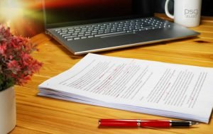 Stack of typed papers on desk with red edits in pen. a red pen is on the wooden table as is a laptop, a mug, and a flower pot with small blooms
