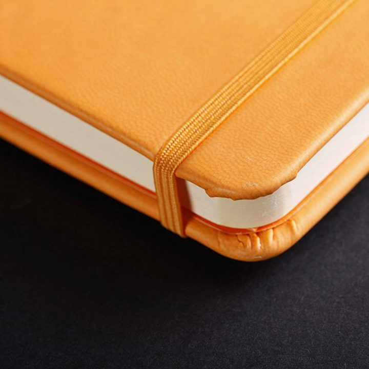 Corner detail of Rhodia webbook, orange cover, closed showing matching elastic. shown on a dark charcoal background.