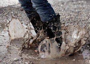 person wearing jeans and boots jumping into a mud puddle and making a splash