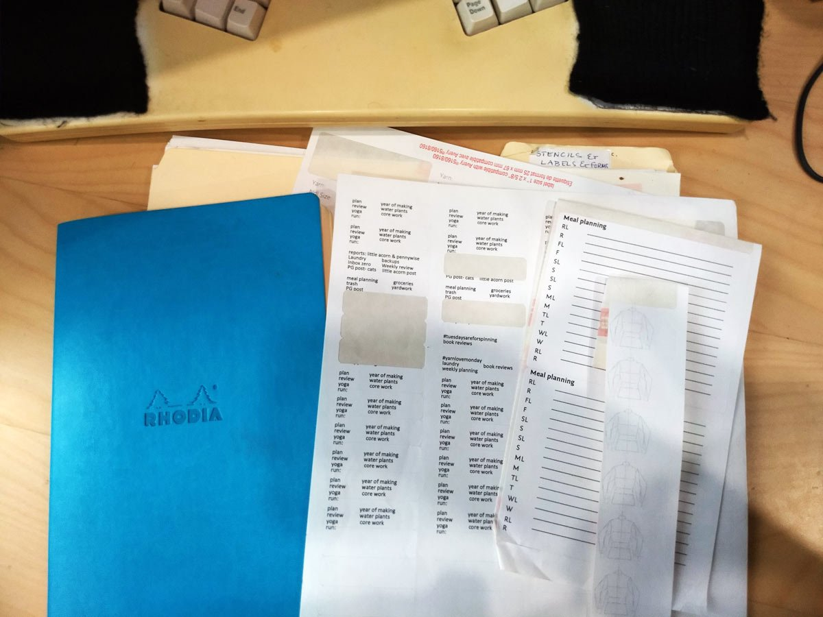 selection of printed labels on a desk with a teal Rhodia notebook next to it.