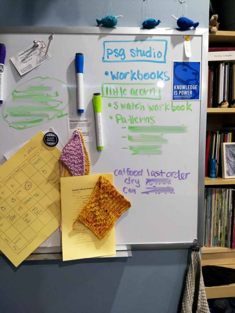 Whiteboard with project notes, last order dates, and various items attached via magnet, knitting swatches and pieces of paper are visible.