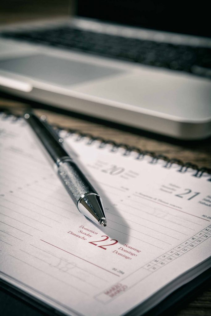 Closeup of a pen over a planner with a laptop on background